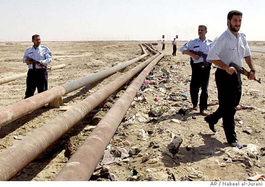Armed Iraqi police patrol along oil pipelines outside of the town of Faw, Iraq Wednesday June 16, 2004. Saboteurs blasted a key pipeline Wednesday for the second time in as many days, halting Iraq's oil exports, officials said. (AP Photo/Nabeel al-Jurani) Photo: NABEEL AL-JURANI
