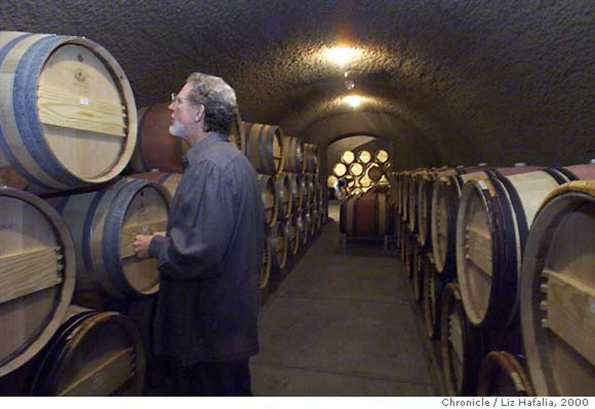 CULTWINES5-C-11DEC00-BU-LH--Top-of-the-line winemaker Bill Harlan checking his winebarrels in the tunnel cellar dug into the hillside of one of his vineyards. Photo by Liz Hafalia/The Chronicle