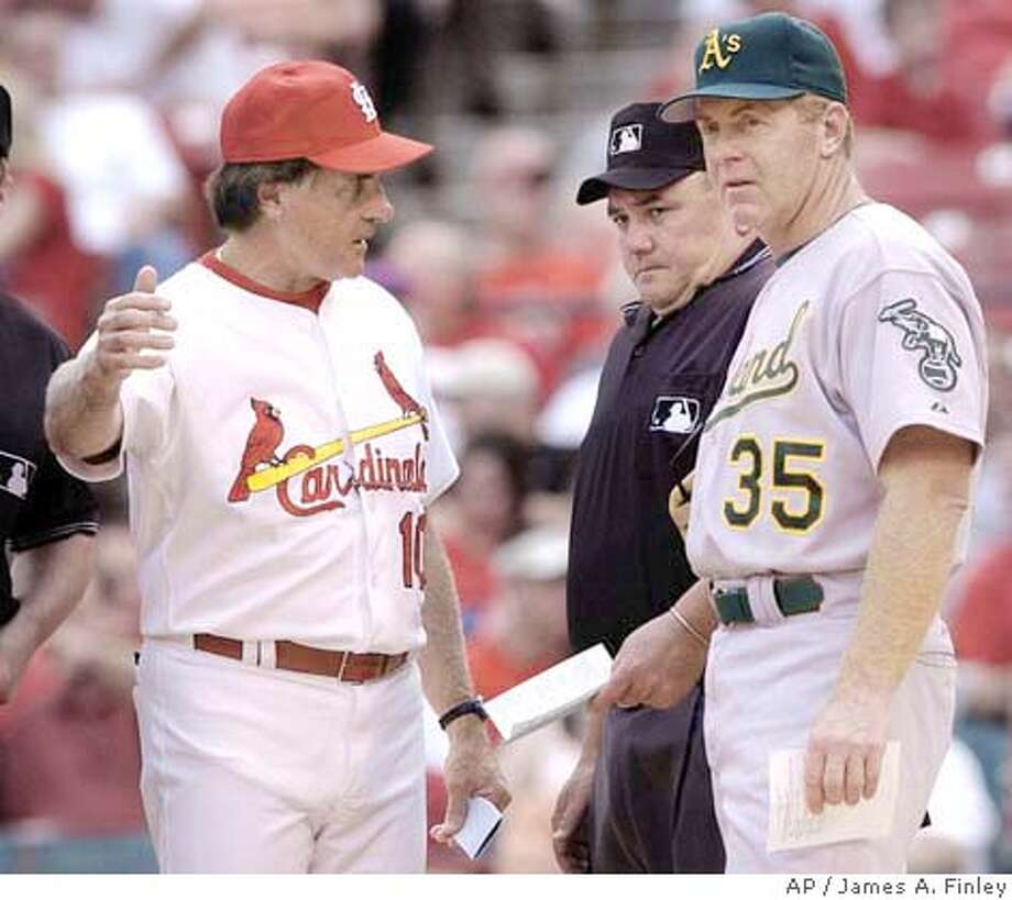 Tony La Russa, manager of the St. Louis Cardinals explains the ground rules to Oakland Athletics coach Brad Fischer (35) before the start of their interleague game in St. Louis. Looking on is home plate umpire Larry Poncino. (AP Photo/James A. Finley) Photo: JAMES A. FINLEY