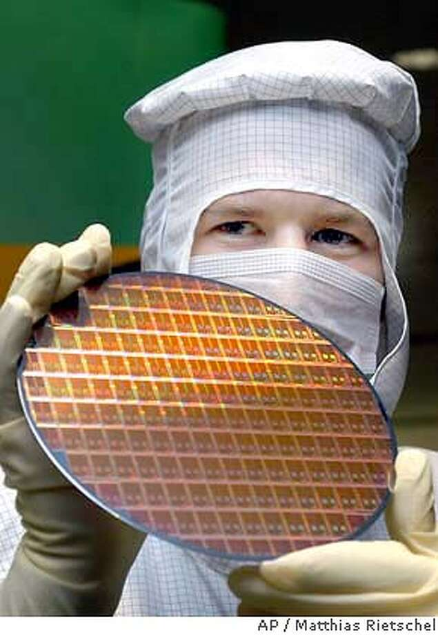 Technician Thomas Altnickel poses with a 200-mm-wafer after a news conference in the AMD factory, Advanced Micro Devices, in Dresden, eastern Germany, Thursday, Nov. 20, 2003. AMD, based in Sunnyvale, California, the semiconductor producer, announced the building of a new manufacturing facility for 300-millimeter wafer production within the next three years in Dresden with costs of US$ 2.4 billion (euro 2 billion). (AP Photo/Matthias Rietschel) CAT Photo: MATTHIAS RIETSCHEL
