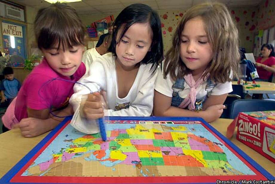 Play time: Sarah Abiharb, center, and friends at the Westwood Day Care Center check out the Geo Safari Search as part of the Great American Toy Test. Chronicle photo by Mark Costantini