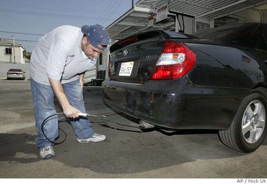 Armen Gharibian at AA VJ's Smog Center prepares to check the emissions of a vehicle Tuesday, June 15, 2004, in Los Angeles. California Gov. Arnold Schwarzenegger announced Tuesday a new plan for fighting smog that would dedicate $61 million a year to reduce air pollution from diesel engines and allow owners of new vehicles to go two extra years without getting smog checks. (AP Photo/Nick Ut) Photo: NICK UT