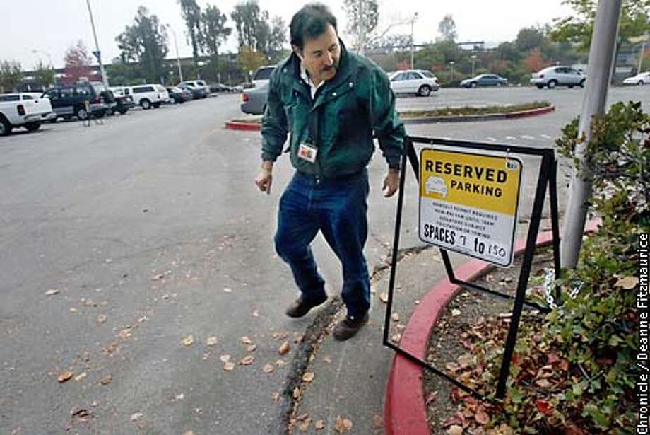 Kevin Hagerty, Manager of Parking Programs for BART walks away from a sign he just set up tp notify people of the new program of reserved parking spaces at BART. This is the Orinda BART station.  CHRONICLE PHOTO BY DEANNE FITZMAURICE Photo: DEANNE FITZMAURICE