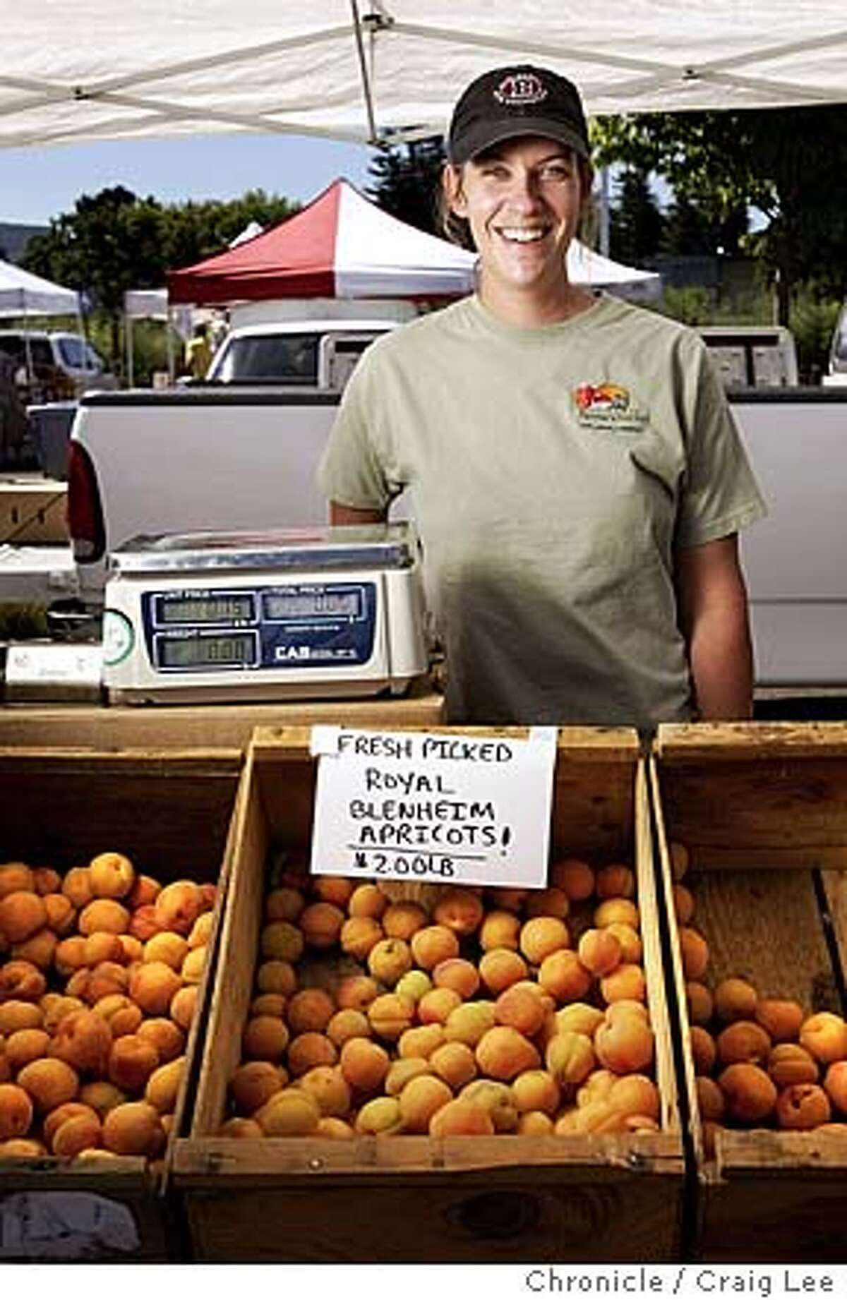 Michele Bera of Bera Ranch and the Blenheim apricots that she sells. Story is about Blenheim apricots (sometimes called Royals or Royal Blenheims) which are delicious and are not produced commercially. This photo was taken at the Napa Farmer's Market in the COPIA parking lot in Napa. Event on 6/8/04 in Napa. Craig Lee / The Chronicle