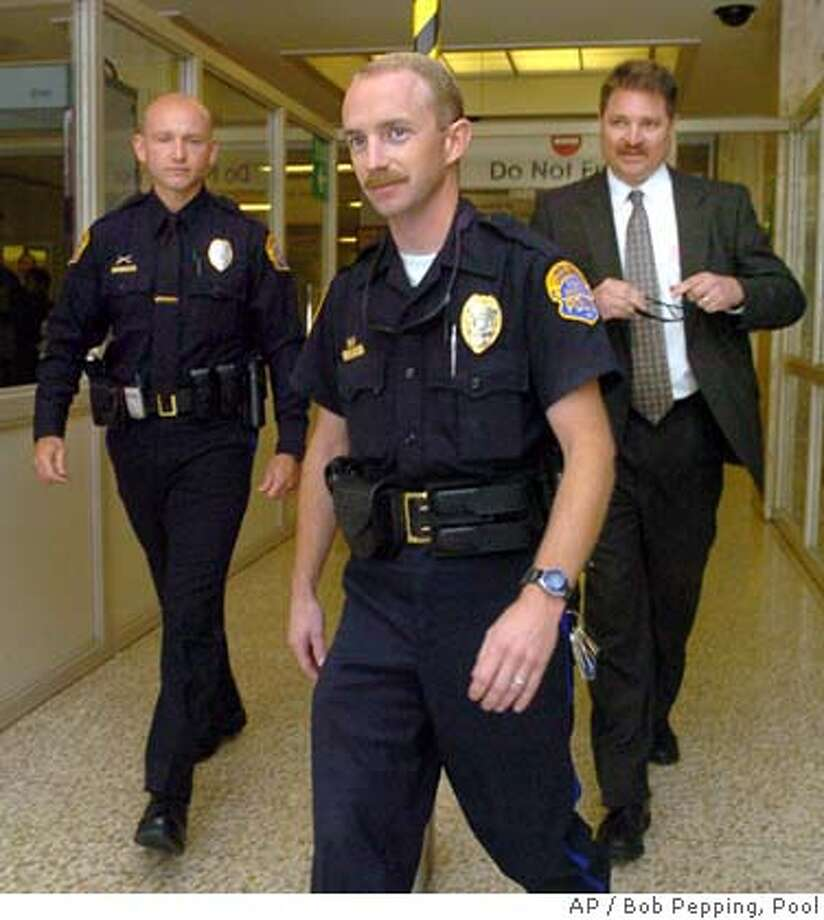 Modesto police officers Derrick Letsinger, center and Matthew Spurlock leave the San Mateo County Courthouse during the lunch break Monday, June 14, 2004, after testifying at the Peterson trial in Redwood City, Calif. At right is Modesto police detective Jon Evers, who is yet to testify. Peterson is charged with the murders of his wife Laci Peterson and their unborn son Connor. (Contra Costa Times/Bob Pepping/Pool) Photo: BOB PEPPING