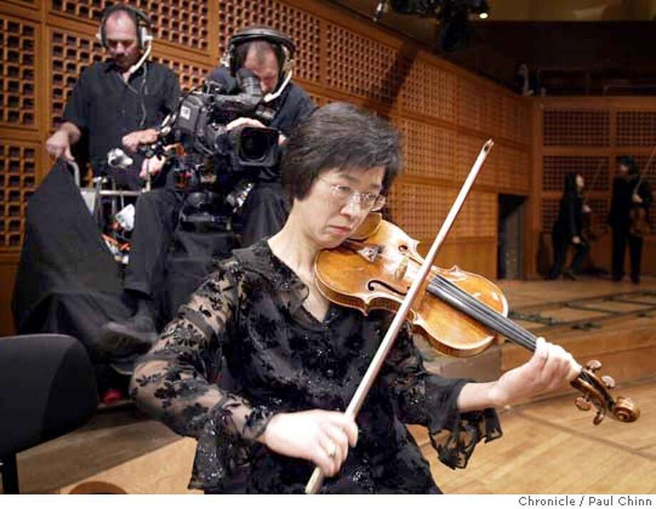 Violinist Yukiko Kurakata warmed up with her instrument as a camera crew prepares for the videotaped production. The San Francisco Symphony videotapes a documentary for PBS at Davies Symphony Hall in San Francisco on 5/13/04. PAUL CHINN/The Chronicle Photo: PAUL CHINN