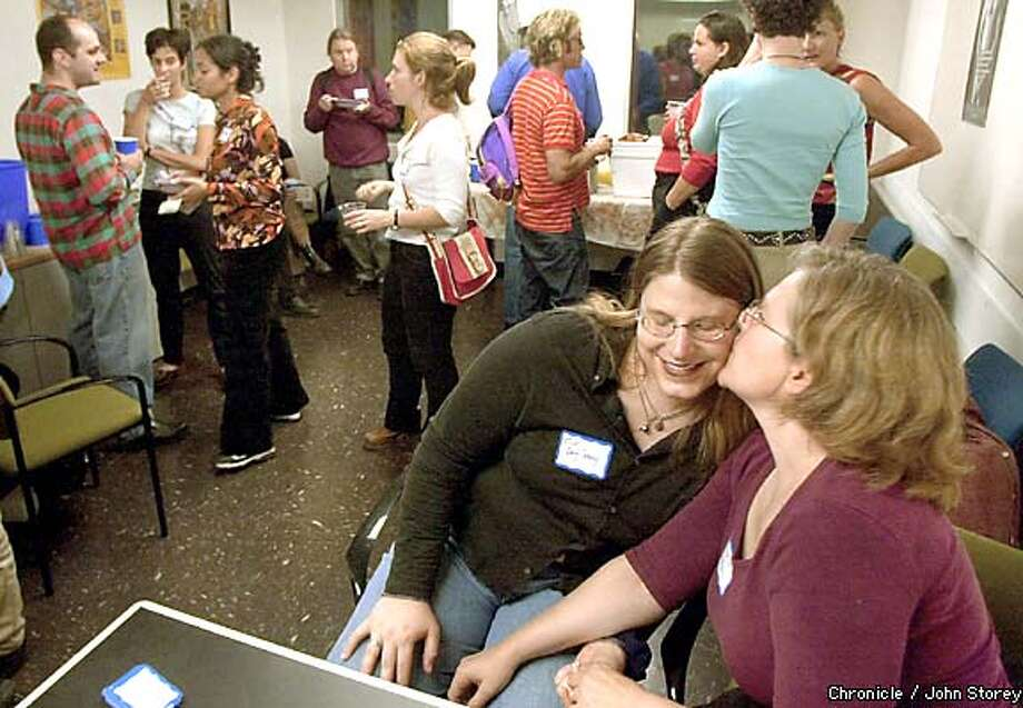 Sweet acceptance: Melissa White gives a kiss to Tracy Kronzak at an ice cream social for bisexuals. Chronicle photo by John Storey
