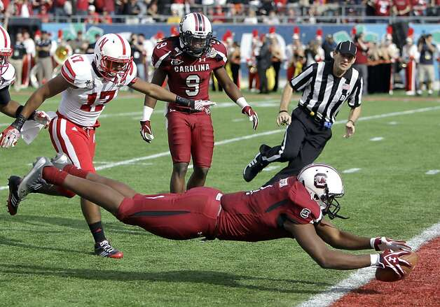 South Carolina wide receiver Alshon Jeffery, right, dives across the goal line past Nebraska cornerback Ciante Evans (17) for a 51-yard touchdown as time expires in the first half of the Capital One Bowl NCAA college football game, Monday, Jan. 2, 2012, in Orlando, Fla. South Carolina won 30-13. (AP Photo/John Raoux) Photo: John Raoux, Associated Press
