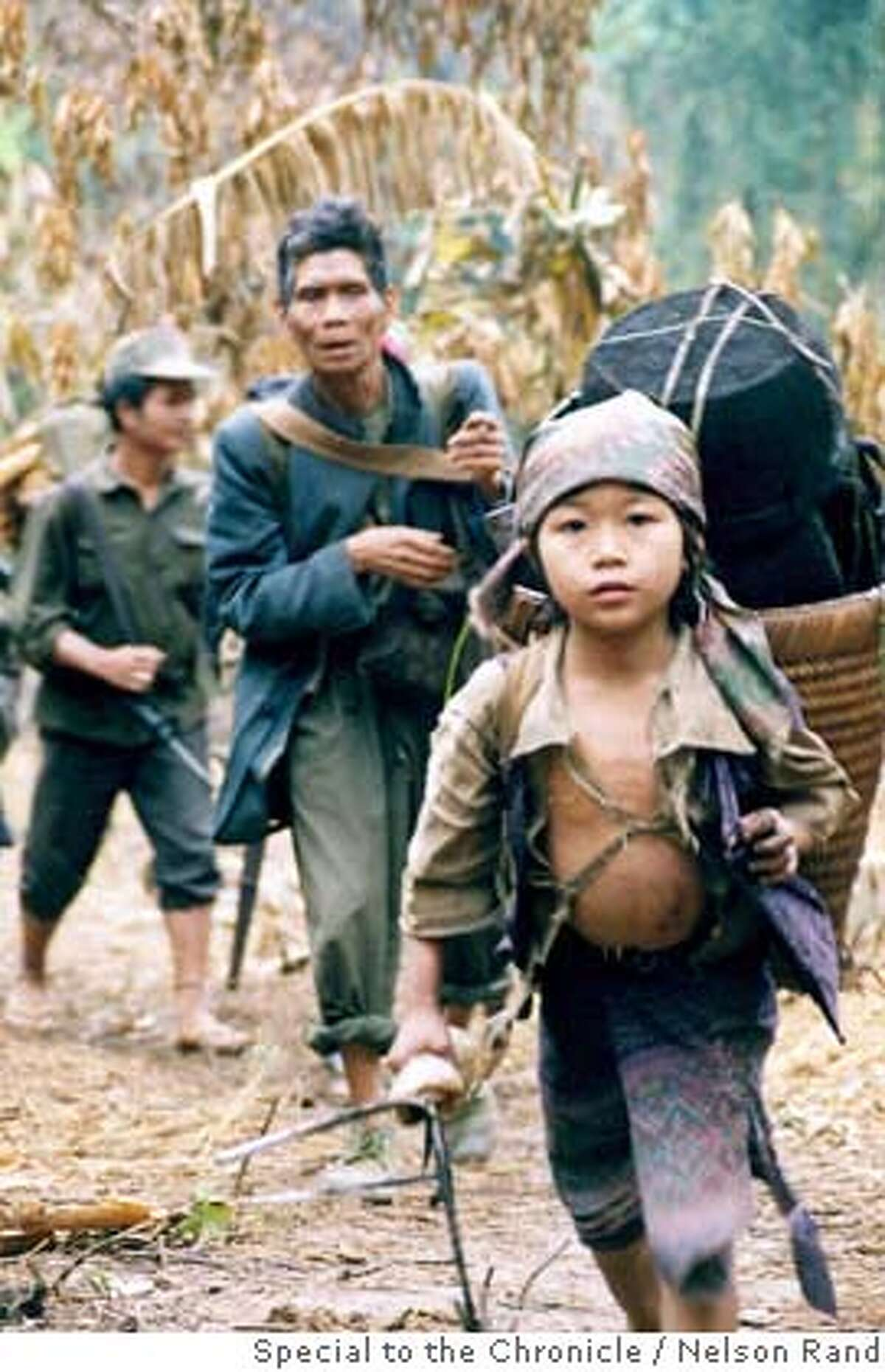 A family walks through the jungle as the group�relocates to avoid Laotian soldiers in the area last month. PHOTO CREDIT: NELSON RAND/SPECIAL TO THE CHRONICLE ONE-TIME USE ONLY!