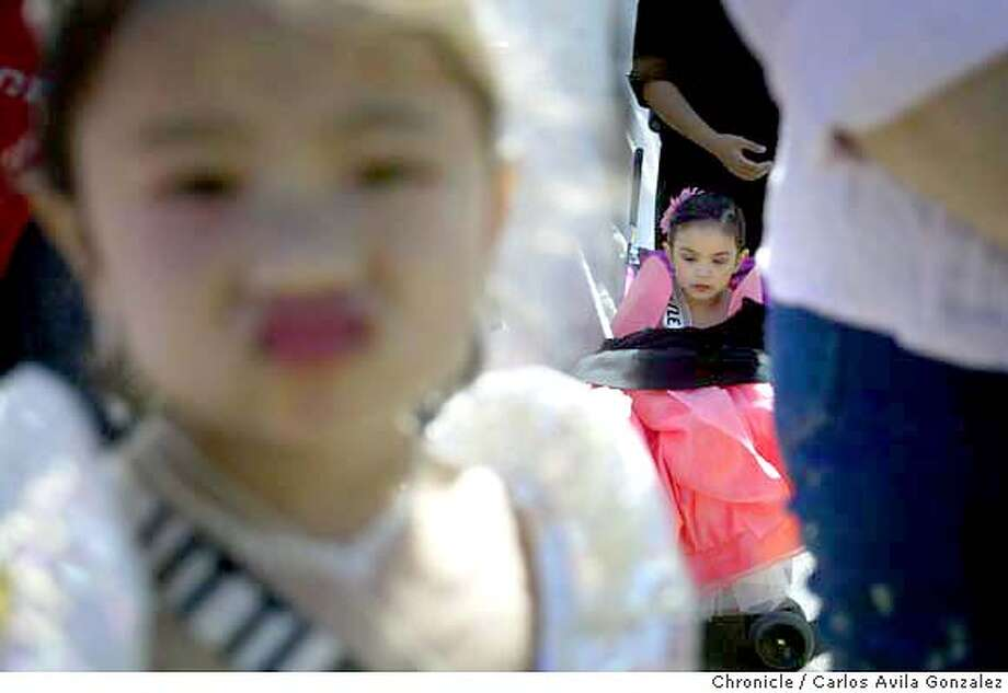 from left: Fides Bernales,3 , Little Miss RP USA FLorida 2004 prepares to line up backstage for the awards presentation as Kiara Deliman, Little Miss RP USA Ohio 2004 , 4, waits backstage in her stroller at Civic Center Plaza. Celebration of Philippine Independence Day with rides, traditional foods and crafts for sale, live entertainment.  Photo taken on 06/13/04, in San Francisco, CA.  Photo By Carlos Avila Gonzalez / The San Francisco Chronicle Photo: Carlos Avila Gonzalez