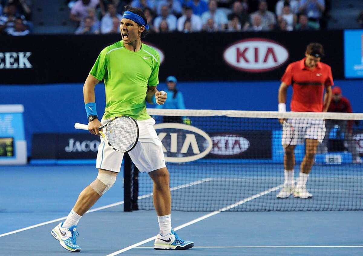 Spain's Rafael Nadal, left, celebrates a point win against Switzerland's Roger Federer during their semifinal at the Australian Open tennis championship, in Melbourne, Australia, Thursday, Jan. 26, 2012. (AP Photo/Joe Castro,Pool)