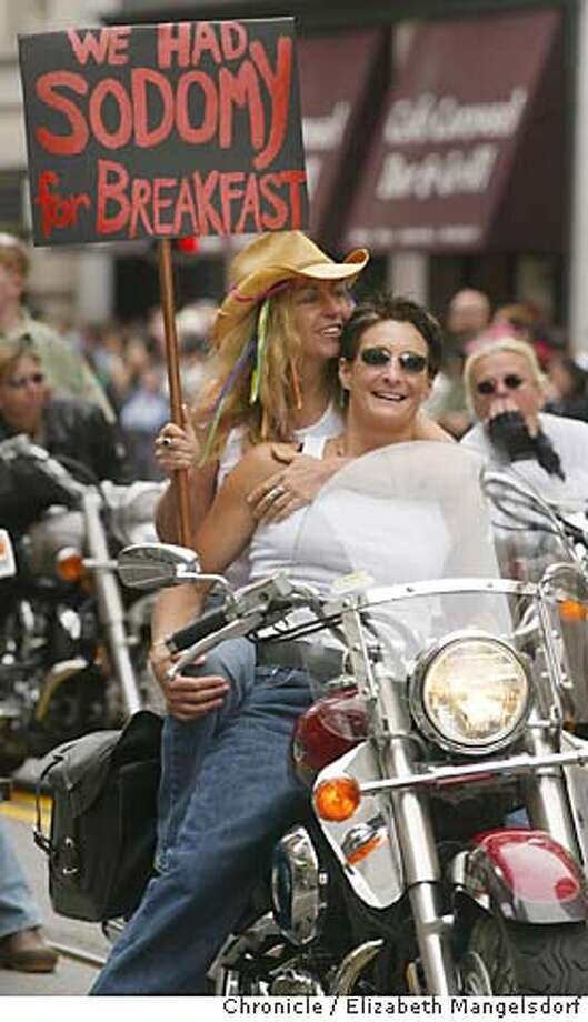 gaypride125_LM.jpg Event on 6/29/03 in San Francisco.  Trace(cq) Cavaretta, front, from SF, and Jill Leslie, with hat, from Sebastapol, wait to ride down the street witht the Dykes on Bikes to start off the parade.  (NOTE: GRAFFIC NATURE OF SIGN)  Gay pride Parade down Market street in San Francisco.  LIZ MANGELSDORF / The Chronicle Photo: LIZ MANGELSDORF