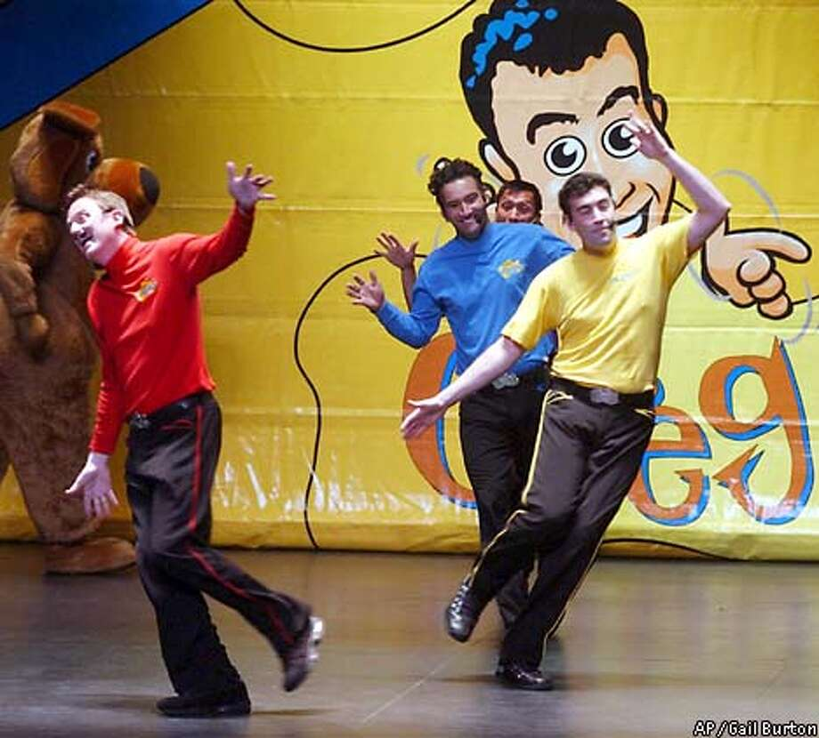 ** ADVANCE FOR WEEKEND EDITIONS, NOV. 28-DEC 1 **The Wiggles, from left, Murray Cook, Anthony Field, Jeff Fatt (partially blocked) and Greg Page perform Saturday, Nov. 16, 2002 in Baltimore. The Australian television musical group has been touring the country, entertaining the under-five set and their parents. A costumed dog performer dances behind them. (AP Photo/Gail Burton) Photo: GAIL BURTON