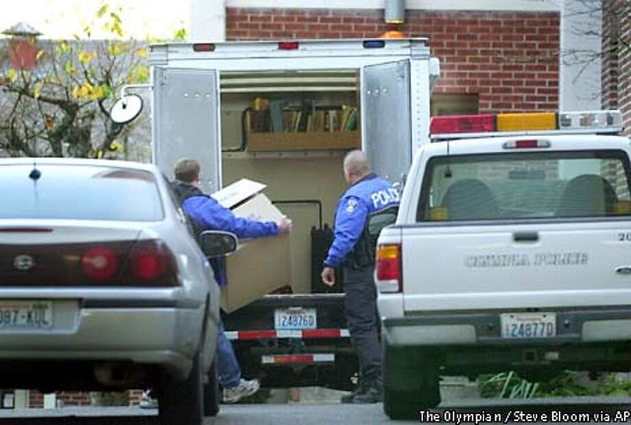Olympia police collect evidence seized Wednesday, Nov. 27, 2002, during a search of the Capitol House apartment of Andrew McCrae in Olympia, Wash. McCrae, 23, of Olympia, a fugitive suspected of killing a California police officer in a crusade against police brutality, was captured Tuesday with the help of a local newspaper reporter. (AP Photo/The Olympian, Steve Bloom) Photo: STEVE BLOOM