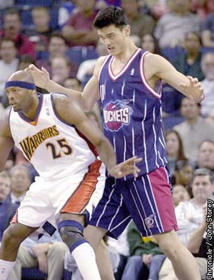 WARRIORS0-C-27NOV02-SP-JRS-The Warriors vs. the Rockets at the Oakland Coliseum. Yao Ming defends against Erick Dampier. Chronicle photo by John Storey. Photo: John Storey