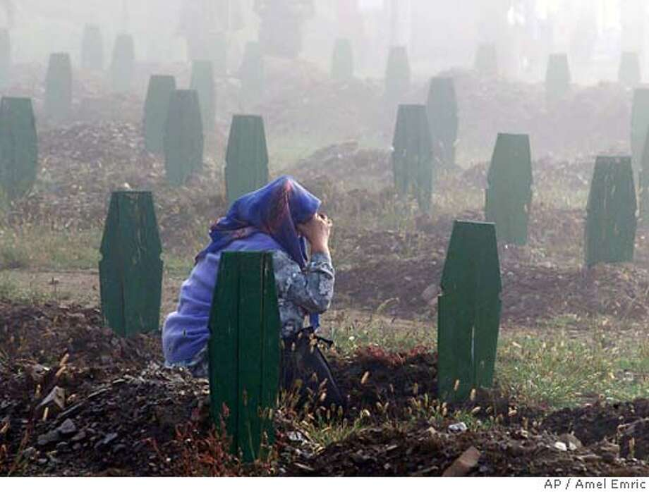 A Bosnian Muslim woman weeps as she squats next to the grave of her relative in the foggy morning during a memorial ceremony for 107 identified victims of the Srebrenica massacre in July 1995, which was part of the official opening ceremony of the Srebrenica-Potocari Memorial and Cemetery that pays tribute to those who were killed in the massacre, in Potocari, northeast of Sarajevo, Saturday, Sept. 20, 2003. Former U.S. President Bill Clinton officially opened the memorial center. (AP Photo/Amel Emric) Ran on: 06-12-2004  A Bosnian woman weeps at the grave of a relative during a memorial in September 2003 for 107 identified victims of the 1995 massacre. Photo: AMEL EMRIC