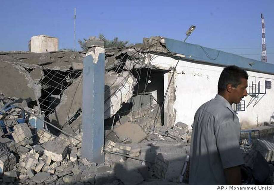 An Iraqi policeman walks through a police station which was destroyed in an explosion in Yusufiyah, Iraq, Friday June 11, 2004. Gunmen stormed the police station south of Baghdad, drove off the poorly armed police and blasted the station in the fourth such attack against Iraqi security installations over the last week, officials and witnesses said. (AP Photo/Mohammed Uraibi) Ran on: 06-12-2004  An Iraqi police officer passes the remains of a police station in Yusufiyah, 12 miles from Baghdad, after attackers entered and blew it up. Photo: MOHAMMED URAIBI