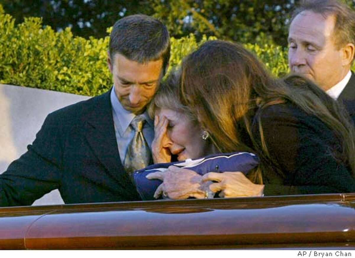 Nancy Reagan, center, is joined by son Ron Reagan, left, son Michael Reagan, second from right, and daughter Patti Davis as she cries over the coffin bearing her husband former President during interment ceremonies for the former president at the Presidential Library in Simi Valley, Calif., Friday, June 11, 2004. (AP Photo/Bryan Chan, Pool)