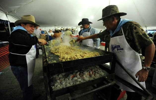 Gabriel Hernandez, left, Eddie Romero and Benito Hernandez prepare the ingredients for breakfast tacos during the annual Cowboy Breakfast at Cowboys Dance Hall on Friday, Jan. 27, 2012. Thousands of tacos, biscuits and gravy, and other foods are served to mark the beginning of rodeo season in San Antonio.  Photo: Billy Calzada, San Antonio Express-News / San Antonio Express-News