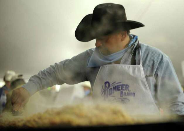Eddie Romero prepares eggs during the annual Cowboy Breakfast at Cowboys Dance Hall on Friday, Jan. 27, 2012. Thousands of tacos, biscuits and gravy, and other foods are served to mark the beginning of rodeo season in San Antonio.  Photo: Billy Calzada, San Antonio Express-News / San Antonio Express-News