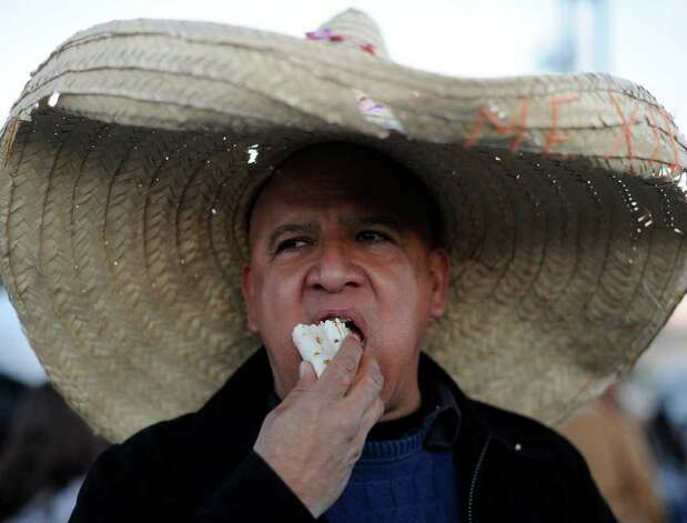 Javier Hernandez eats a taco during the annual Cowboy Breakfast at Cowboys Dance Hall on Friday, Jan. 27, 2012. Thousands of tacos, biscuits and gravy, and other foods are served to mark the beginning of rodeo season in San Antonio. Photo: Billy Calzada, San Antonio Express-News / San Antonio Express-News