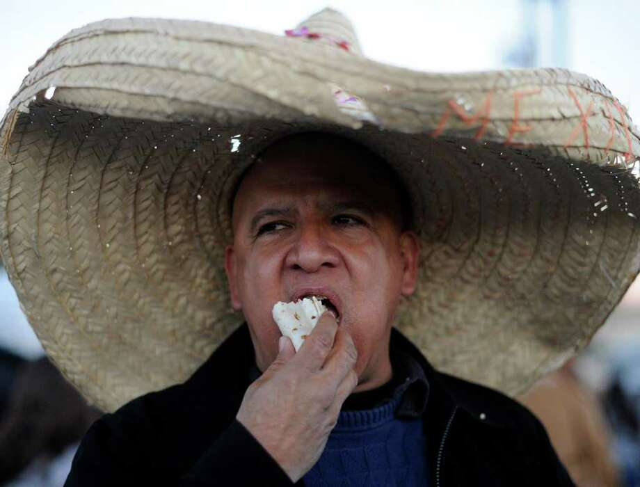 Javier Hernandez eats a taco during the annual Cowboy Breakfast at Cowboys Dance Hall on Friday, Jan. 27, 2012. Thousands of tacos, biscuits and gravy, and other foods are served to mark the beginning of rodeo season in San Antonio. BILLY CALZADA / San Antonio Express-News Photo: Billy Calzada, San Antonio Express-News / San Antonio Express-News