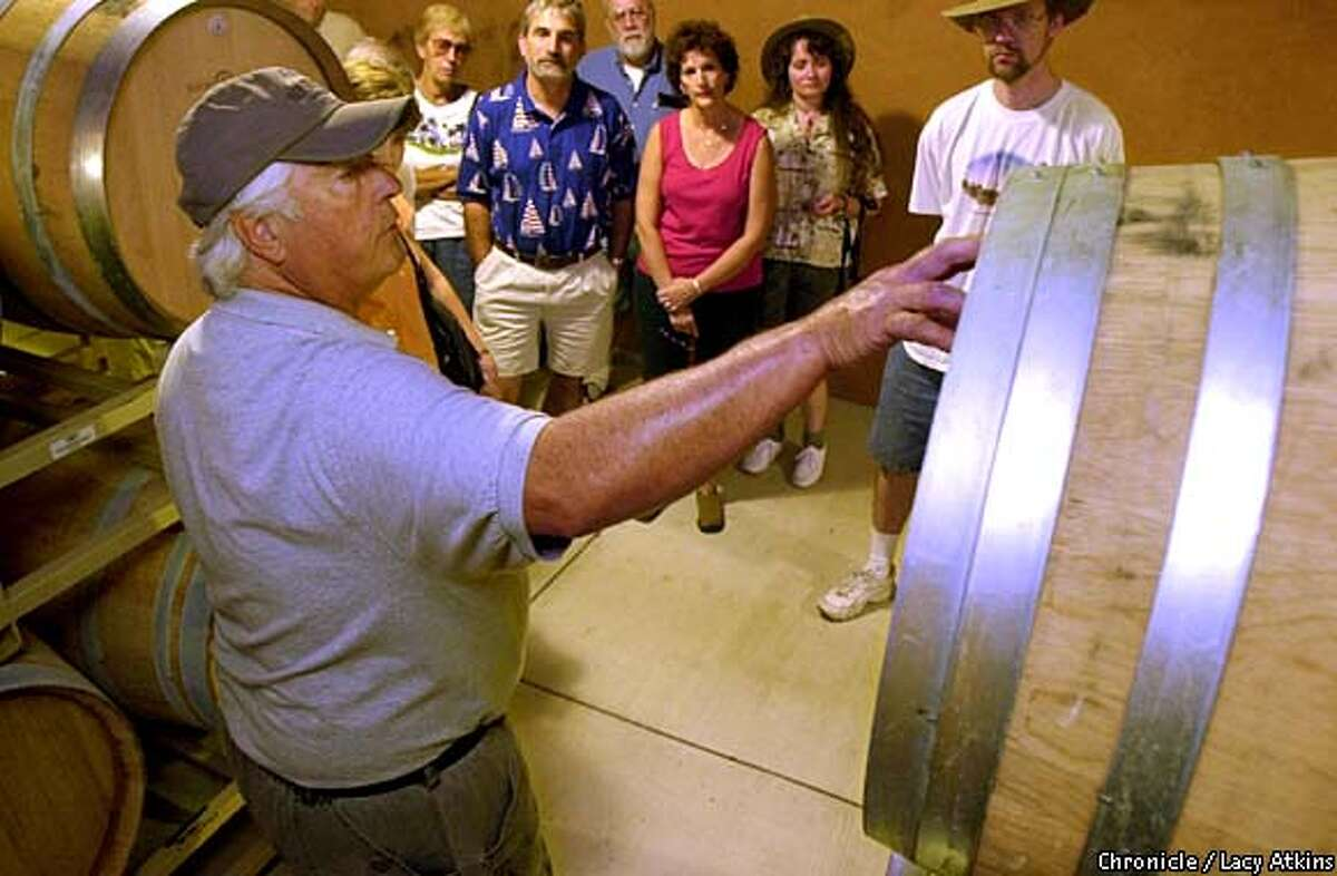 Jerry Dion, tour host at Benziger, shows a group the barrel-aging room. Chronicle photo by Lacy Atkins