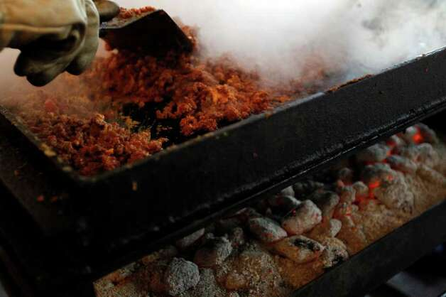 Meat is cooked over coals during the 34th annual Cowboy Breakfast at Cowboys Dance Hall on Friday, Jan. 27, 2012. Photo: Michael Miller, San Antonio Express-News / San Antonio Express-News