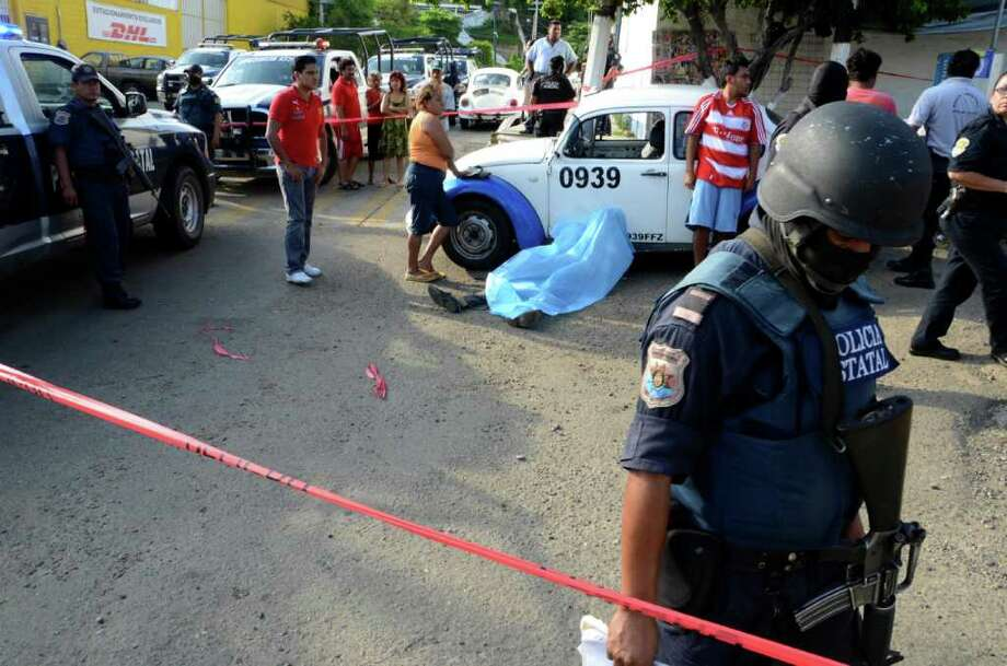 A police officer inspects the crime scene where a man was shot dead in the Pacific resort city of Acapulco, Mexico, Friday Aug. 5, 2011. The city of Acapulco has been hit by violence as drug gangs continue to battle for control of the region. Photo: AP