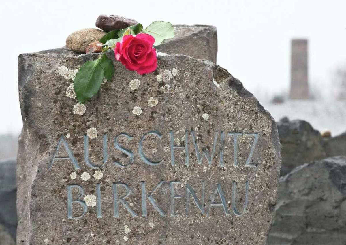 A lone flower tribute lays on a memorial stone in front of the crematorium during the international Holocaust remembrance day in the former Nazi concentration camp Buchenwald near Weimar, central Germany, on Friday. More than 250,000 people were held captive in the camp between 1937 and 1945, and more than 50,000 of them died during that time. Jan. 27 1945, the Soviet army liberated the largest Nazi death camp at Auschwitz-Birkenau, Poland, where more than 1 million prisoners were killed.
