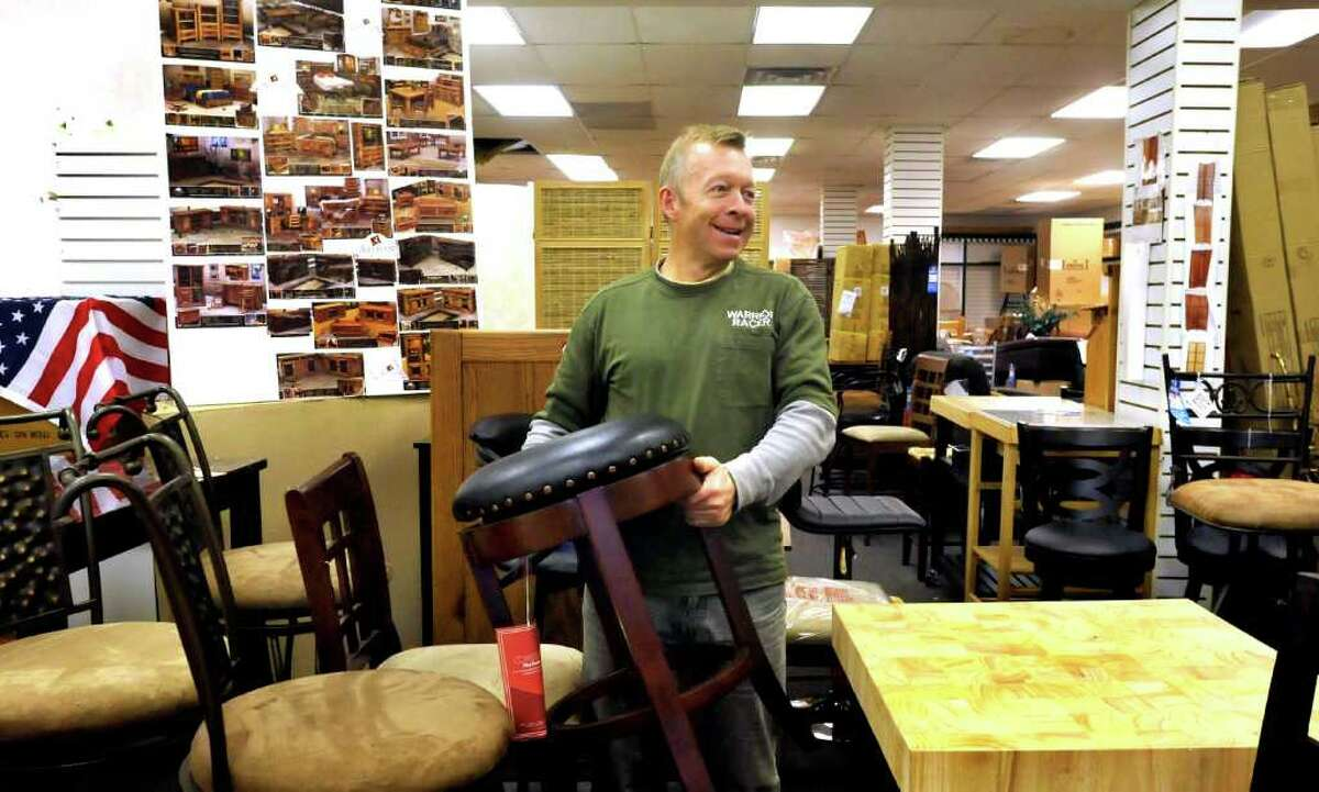 Doug Hughes holds a bar stool in his Brookfield business, Dougs Furniture Barn Friday, Jan. 27, 2012.