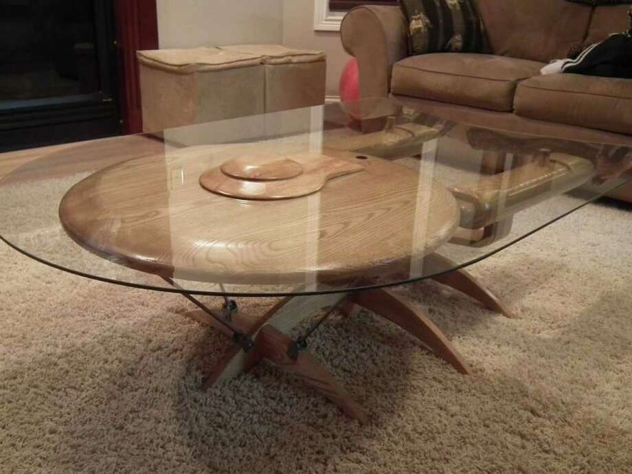 "Looking for the perfect gift for your favorite geek? You can buy this Star Trek Enterprise coffee table for $3,100. ""This is one of the hardest pieces I have ever created,"" carpenter Barry Shields, of Sevierville, Tenn., wrote on his website. ""It took more than three weeks to build the ship."" He made the ship base from ash, poplar and cherry wood, with quarter-inch glass on top. It took two tries to cut the glass the way he wanted. ""The glass is cut to look as though it's in motion and the base was designed to portray the ship in orbit over a planet,"" Shields wrote. He put the bridge atop the glass to make it look like the ship was coming through the glass. The table weighs nearly 75 pounds and is 34 inches wide, 54 inches long and 17 inches high. Why did Shields make it? ""I grew up watching Star Trek and all the other spin offs, like 'Deep Space Nine' and 'The Next Generation,' so thought I would try something different, mainly just to see if I could do it and make something really cool,"" he explained. Which of the many Enterprises is it? Guess now and find the answer with the last of the eight photos in this gallery. Hat tip to inhabitat. Photo: Barry Shields Creations"