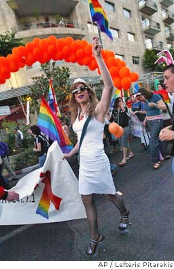 A drag queen dressed as a nurse holding a rainbow-colored flag parades along with hundreds of people participating in a gay pride parade in downtown Jerusalem, Thursday June 3, 2004. (AP Photo/Lefteris Pitarakis) A drag queen dressed as a nurse waves a rainbow flag as he marches in a gay pride parade in downtown Jerusalem. A drag queen dressed as a nurse waves a rainbow flag as he marches in a gay pride parade in downtown Jerusalem. Photo: LEFTERIS PITARAKIS