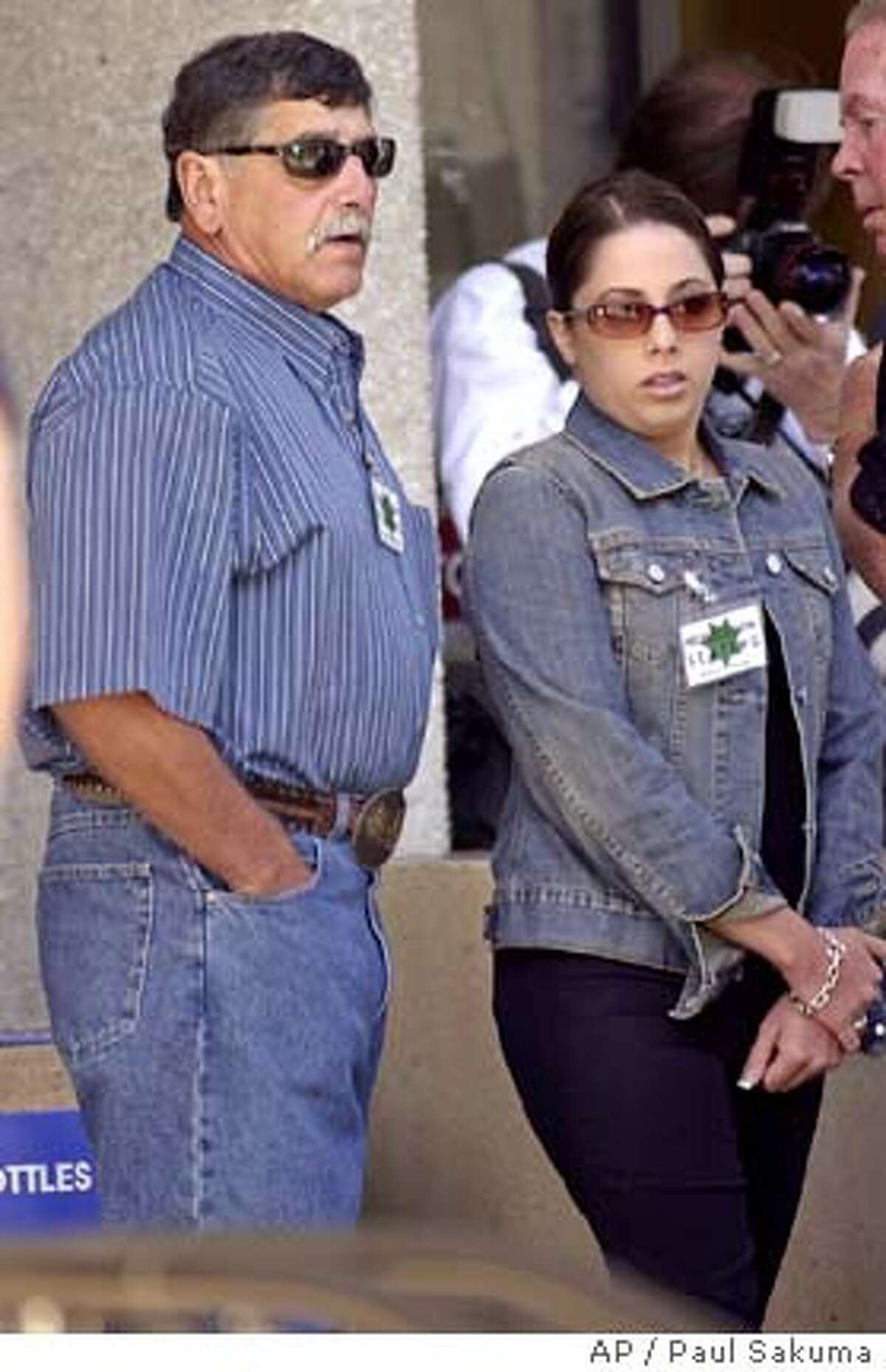 Dennis Rocha, left, father of , arrives with an unidentified woman for the Scott Peterson trial in Redwood City, Calif., Wednesday, June 2, 2004. Peterson is the Modesto, Calif., man who could face the death penalty if convicted of two counts of murder for the deaths of his wife, , and their unborn child. (AP Photo/Paul Sakuma)