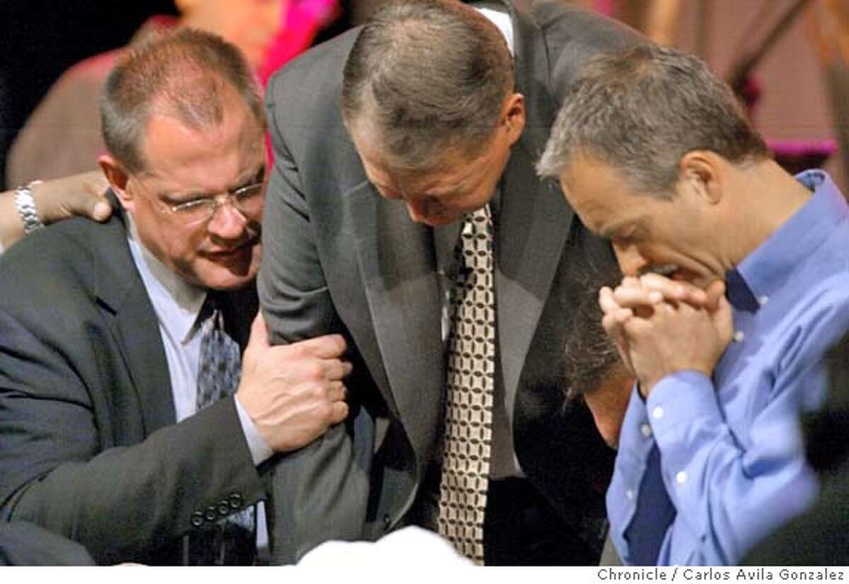Paul Risser, center, is prayed for by other church leaders after his mea culpa speech before a crowd of thousands at the International Church of the Foursquare Gospel's Annual Convention at the San Francsico Hilton in San Francisco, Ca., on Tuesday, June 1, 2004. Risser stepped down as president of the church after a bad investment cost the church a lot of money. Photo taken on 06/01/04 in San Francisco, Ca. Photo By Carlos Avila Gonzalez / The San Francisco Chronicle