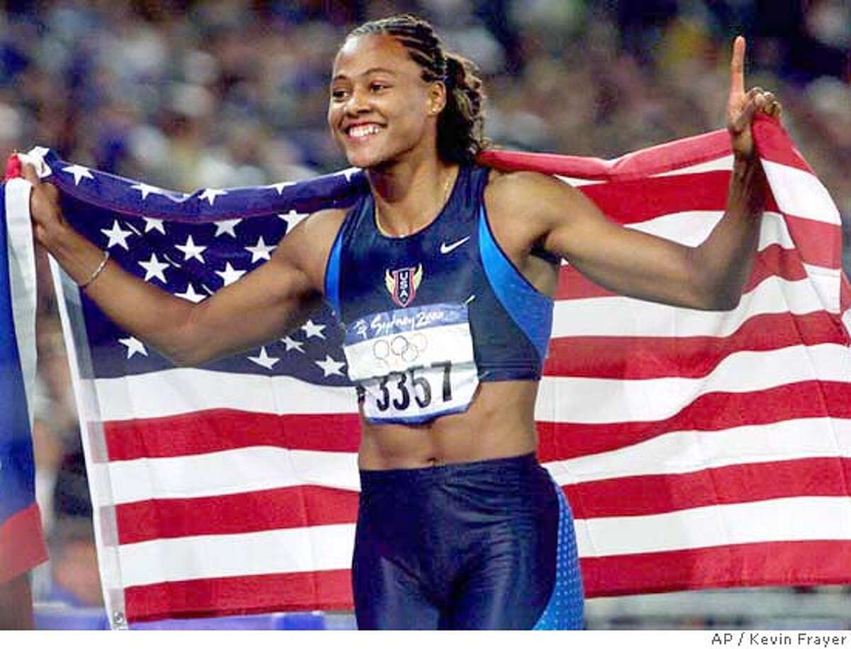Sprinter Marion Jones of the United States celebrates with an American flag after winning the gold medal in the 100 meters at the Olympics in Sydney, Australia Saturday, September 23, 2000. Jones won with a time of 10.75 seconds. (AP Photo/CP, Kevin Frayer) DIGITAL IMAGE
