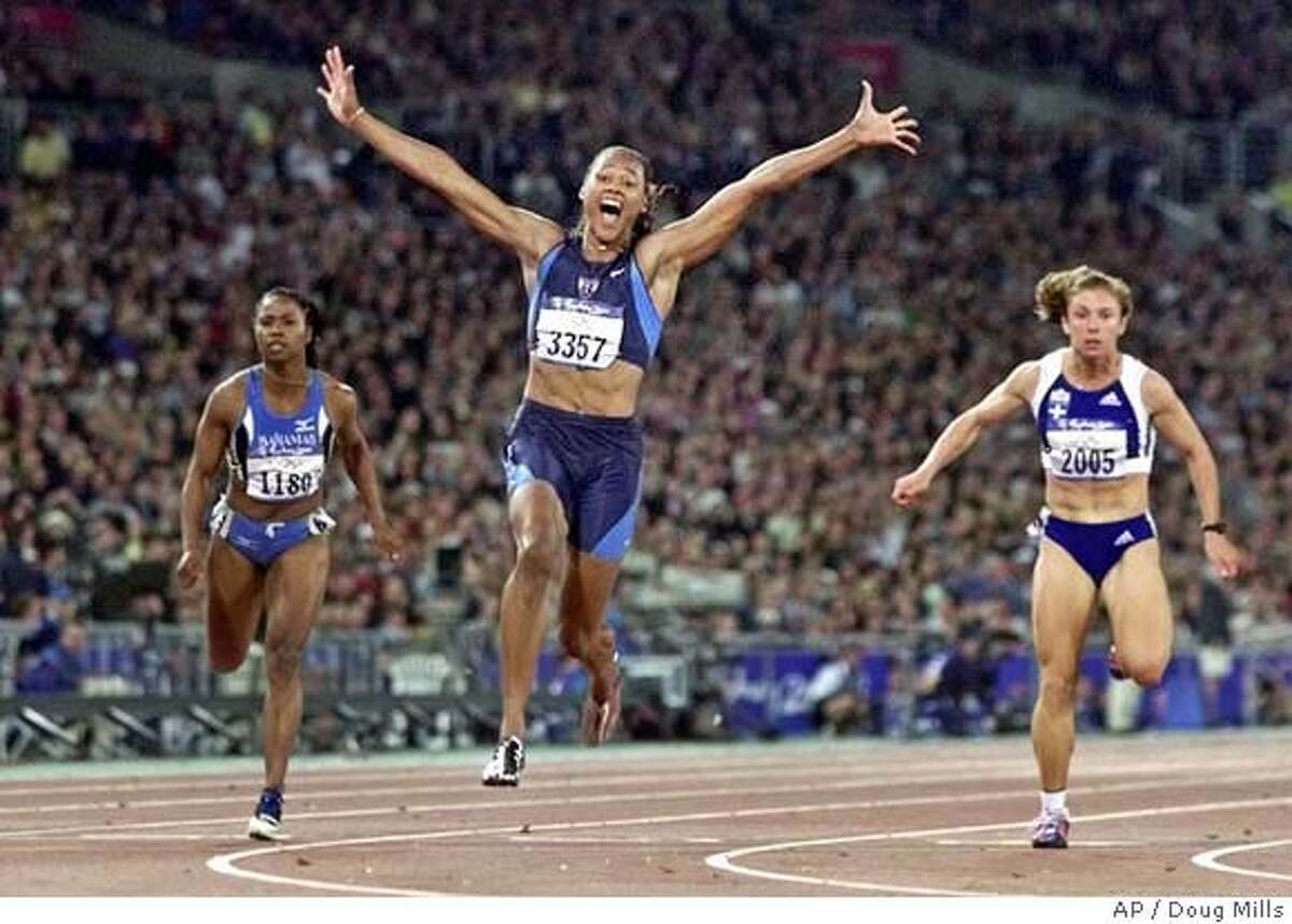FOR USE WITH YEAREND SPORTS STORIES--Marion Jones of the United States, center, celebrates as she crosses the finish line to win the women's 100 meters at Olympic Park during the 2000 Summer Olympics in Sydney, Saturday, Sept. 23, 2000. At left is Chandra Sturrup of the Bahamas and at right is Ekaterini Thanou of Greece who won the silver. (AP Photo/Doug Mills) DIGITAL IMAGE