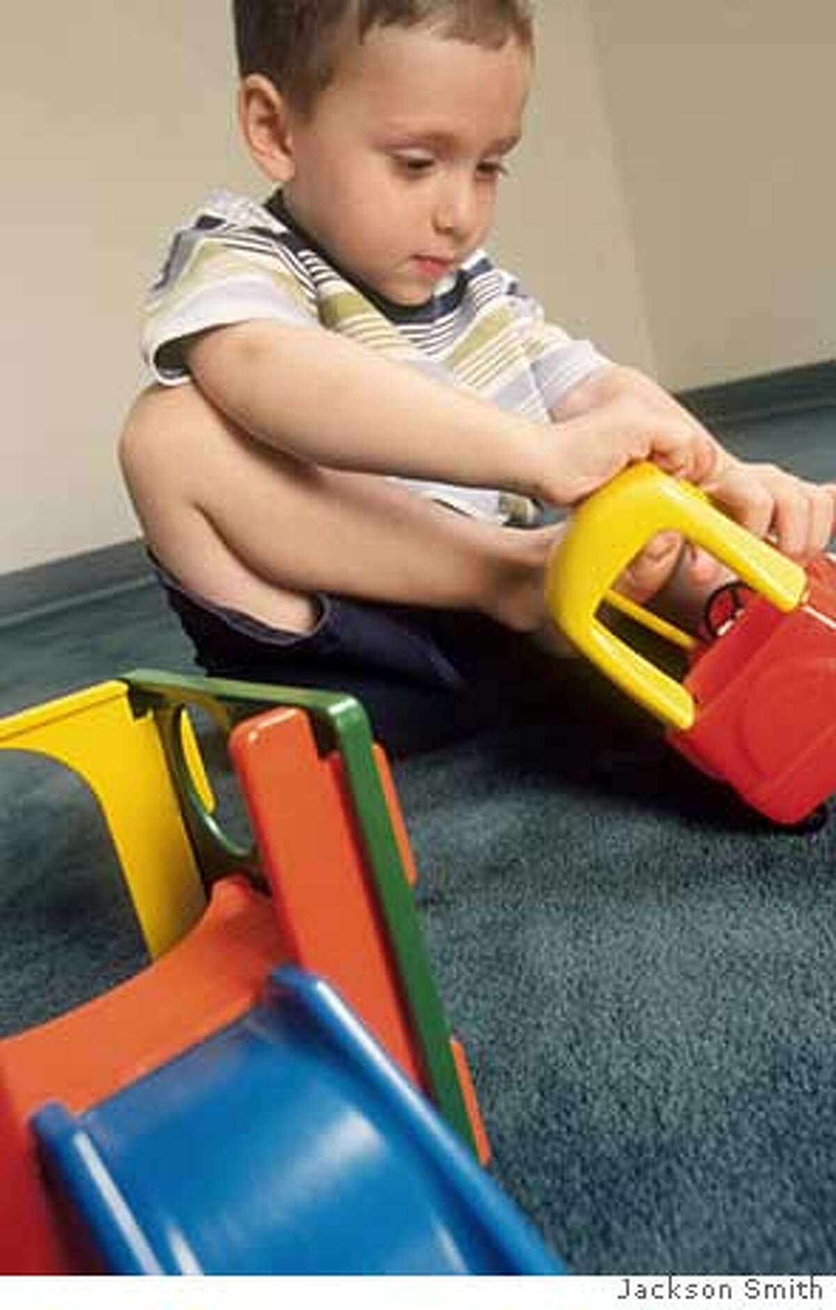 """This photo illustrates how children make """"scale errors"""" � they try to climb into a toy car or sit down on a toy chair because they haven't yet gained the ability to judge the scale of objects. PHOTO CREDIT: JACKSON SMITH"""
