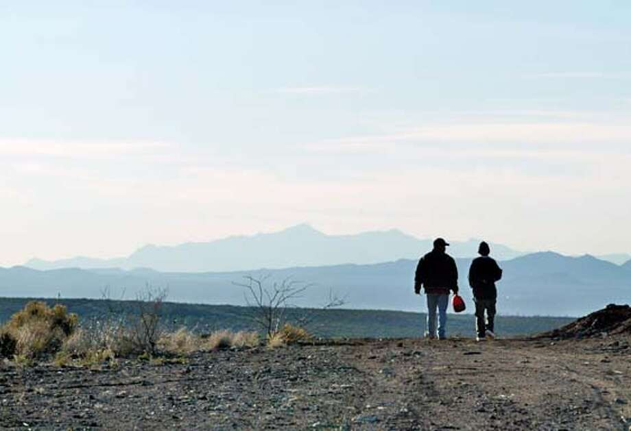 Joaquin Hurtado, left, and his nephew, Martin Murieta, 14, make their way west toward Agua Prieta, Sonora, Mexico on Thursday, February 26, 2004. The two had tried unsuccessfully to cross several times before, and were determined to keep trying, despite having been robbed at gunpoint along the way. Along the Arizona border with Mexico, Grupo Beta takes to the roads, deserts, and rural areas to find and counsel the hundreds of thousands that struggle to find a better life in the U.S. With fewer than 10 people patrolling the area, giving the immigrants aid and information is a daunting task. The aim is not to stop the immigrants, but to give them alternatives to the dangerous trek north. If immigrants fail in their plans, the group also provides funds to those who chose to go home again. Photo taken on 02/26/04 in Agua Prieta, Sonora Photo by Carlos Avila Gonzalez/ The San Francisco Chronicle. Photo: Carlos Avila Gonzalez