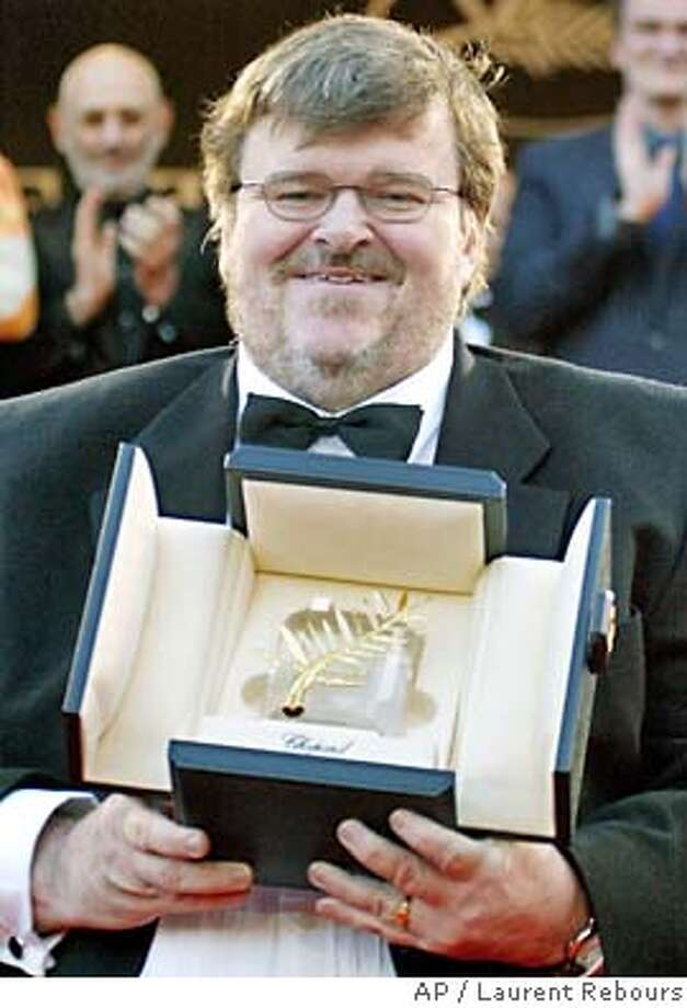 "American film director Michael Moore holds his Palme d'Or award for his documentary film ""Farenheit 911"" as he climbs the steps of the festival palace during the closing ceremony of the 57th International Film Festival in Cannes, southern France, Sunday May 23, 2004. (AP Photo/Laurent Rebours) Photo: LAURENT REBOURS"