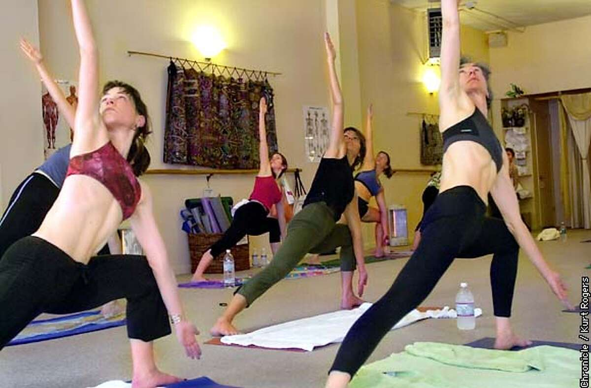 Bikram's Yoga College of India in Burlingame . The class is doing the triangle pose. Photo By Kurt Rogers