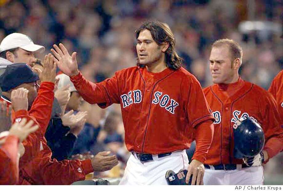 Boston Red Sox Johnny Damon, center, and teammate Kevin Youkilis, right, are congratulated by teammates after being driven home on a three-run, single by Mark Bellhorn in the fourth inninng against the Oakland Athletics at Fenway Park in Boston, Wednesday May 26, 2004. (AP Photo/Charles Krupa) Photo: CHARLES KRUPA
