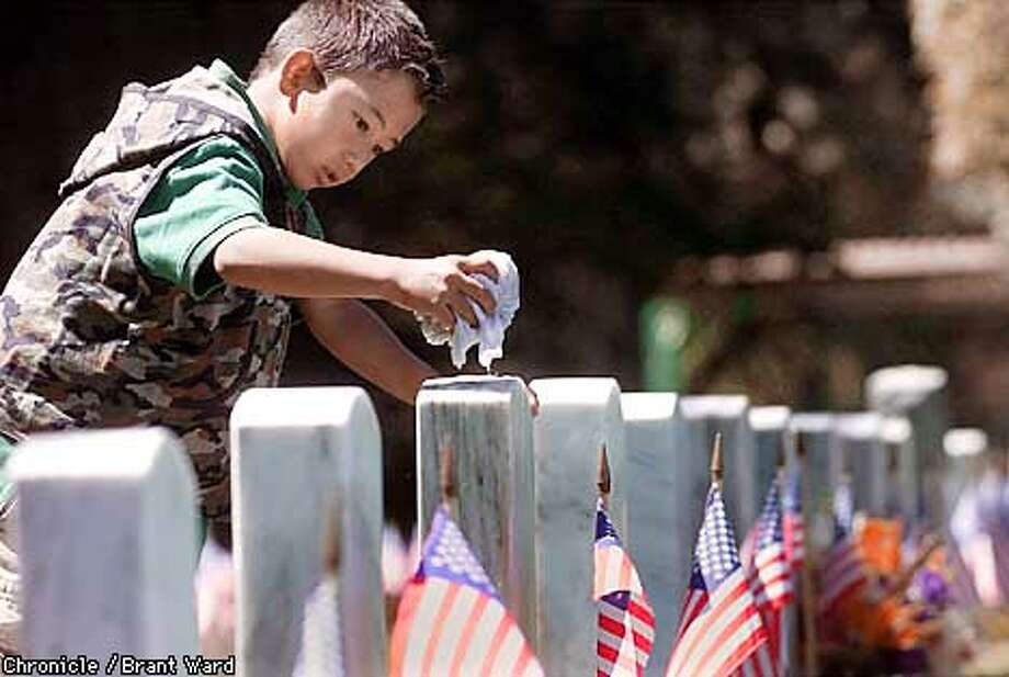 Hiro Sparks, 8, of San Francisco thought the best way to respect those fallen in previous wars, was to wash the tombstones of the veterans. He carried a white bucket through the National Cemetery at the Presidio in San Francisco washing off headstones during Memorial Day. By Brant Ward/Chronicle MANDATORY CREDIT. NO MAGS. NO RESALES Photo: BRANT WARD