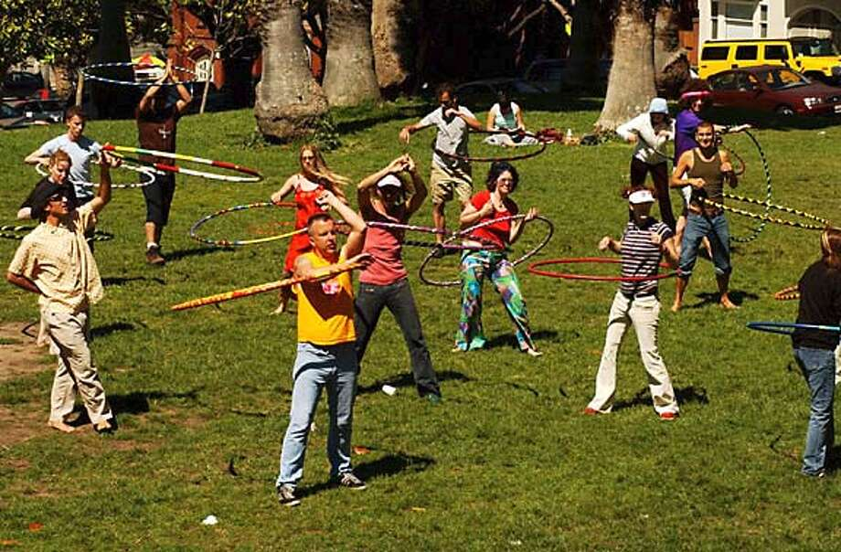tons of fun hoopiing in the park. Philo in front, in yellow tee shirt. Philo Hagen has created a Hula Hooping renaissance. Shown here in Dolores Park.  photo taken on 5/9/04 in San Francisco, CA.  must credit photo by Penni Gladstone/ MANDATORY CREDIT FOR PHOTOG AND SF CHRONICLE/ -MAGS OUT Photo: Penni Gladstone