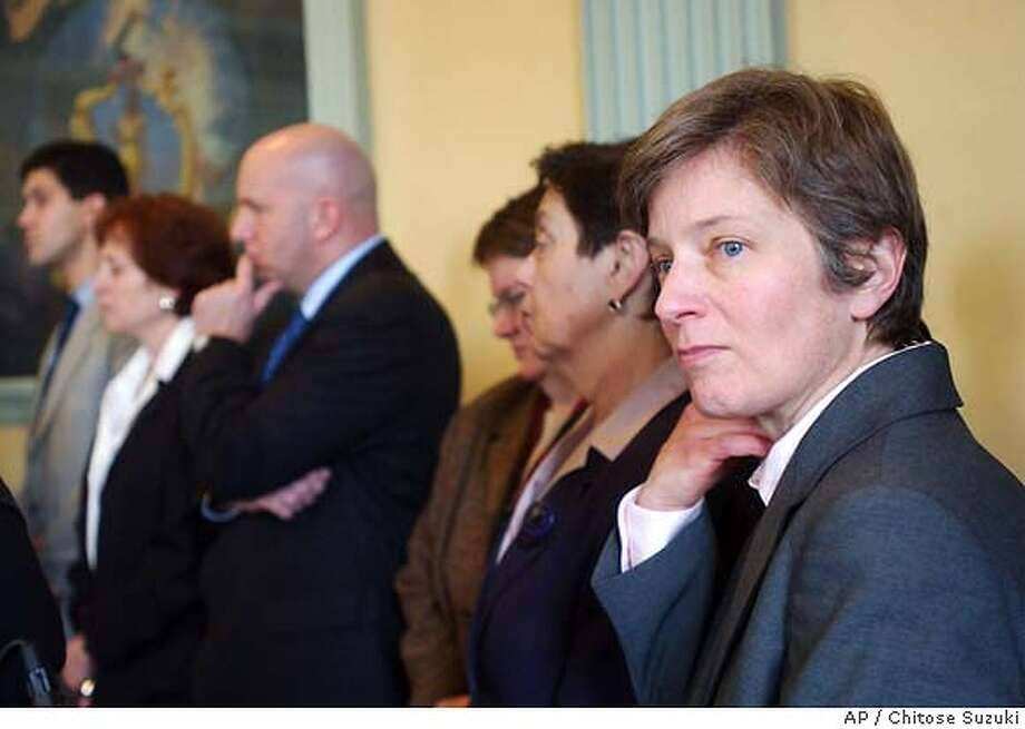 Mary Bonauto, right, the attorney for the plaintiffs in the Massachusetts gay marriage lawsuit, listens to speakers during a news conference at the Massachusetts Statehouse in Boston, Tuesday, March 30, 2004. Gov. Mitt Romney wants the state's highest court to put gay marriages on hold now that the legislature has backed a proposed constitutional amendment to bar them. But the state's Democratic attorney general is balking at making the request. (AP Photo/Chitose Suzuki) Photo: CHITOSE SUZUKI