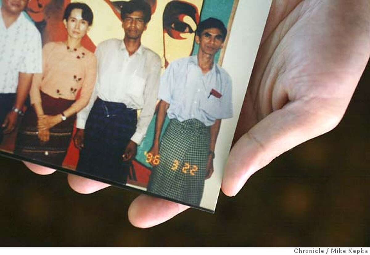 Koko Maung holds a picture of his father (right) and several other members of a political party in Burma, including Aung San Suu Kyi (left), the party leader, just before they were arested and sentenced as political prisoners. Koko Maung, 24, of San Jose came to the United States seeking political asylum after his father was sentenced to 10 years for as a political prisoner in Burma. Maung (who has since moved out to own place) came to live with his aunt and Uncle in Sunnyvale who are also political asylees. Mike Kepka / The Chronicle