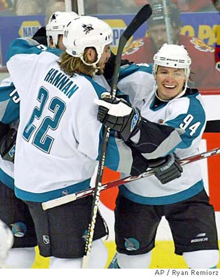 San Jose Sharks' Alexander Korolyuk (94) and Scott Hannan celebrate the first of Korolyuk's two goals against the Calgary Flames during third period of game three of the NHL Western Conference final in Calgary Thursday, May 13, 2004. The Sharks beat the Flames 3-0 and trail 2-1 in the best-of-seven series.(AP Photo/CP, Ryan Remiorz) COM Photo: RYAN REMIORZ