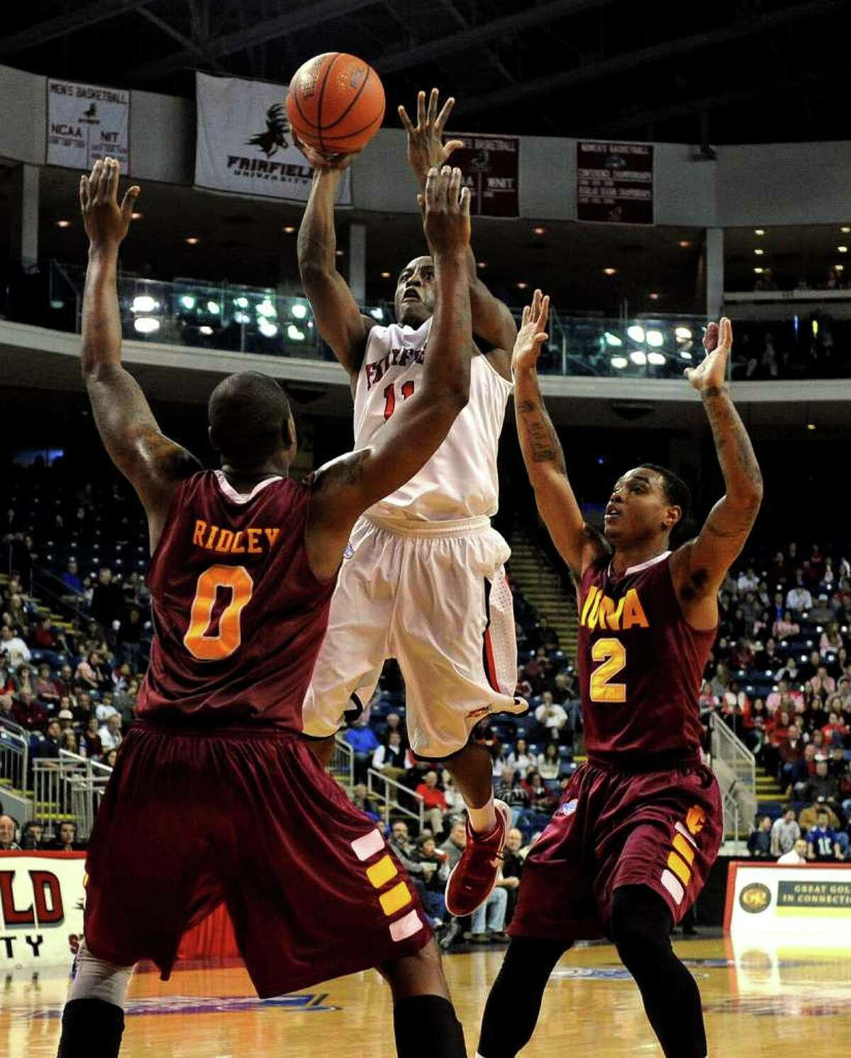 Fairfield University's #11 Desmond Wade attempts a jump shot between Iona's #0 Taaj Ridley and #2 Lamont James, during men's basketball action at the Webster Bank Arena in Bridgeport, Conn. on Friday January 27, 2012.