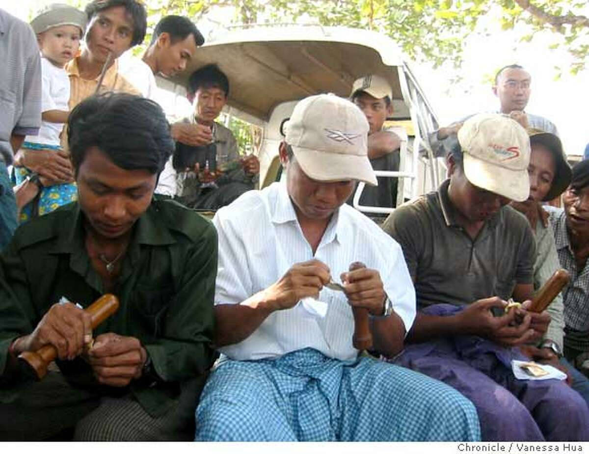 Pedicab drivers learn how to put on condoms during a session sponsored by Population Services International in Burma. Chronicle photo by Vanessa Hua