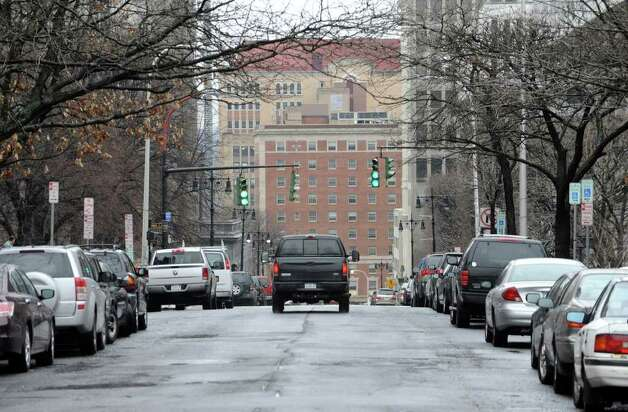 A car looks for a parking spot along State St. Friday Jan. 27, 2012 in Albany, N.Y.  Albany's Common Council is ready to schedule a vote on the creation of the long-desired parking permit system. (Lori Van Buren / Times Union) Photo: Lori Van Buren